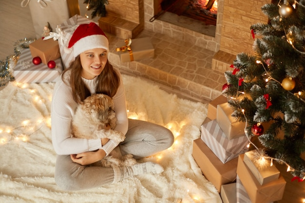 Cute adorable woman sitting on floor on soft carpet with pekingese dog in hands, looking away, wearing casual attire and red hat, posing in festive room with x-mas tree and fireplace.