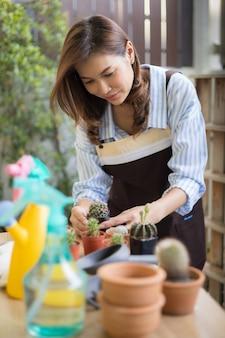 趣味とリラックスした時間を幸せに家でサボテンの小さな鍋を保持し、配置するエプロンを身に着けているかわいい大人のアジアの女性。