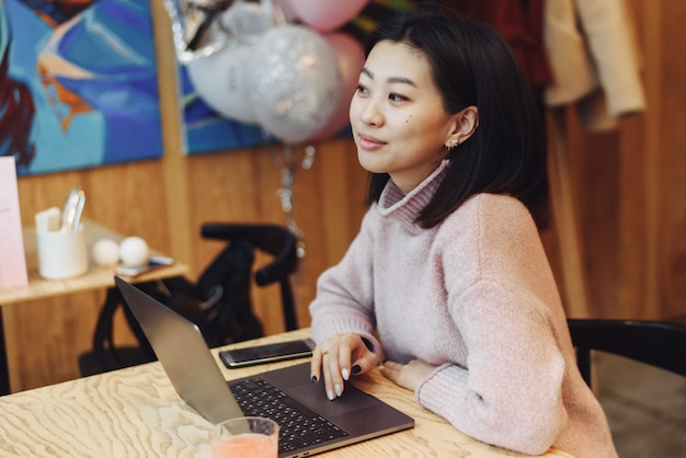 Cute adult girl plays in a laptop in a coffee shop. asian woman working in a cafe at a laptop. freelance concept