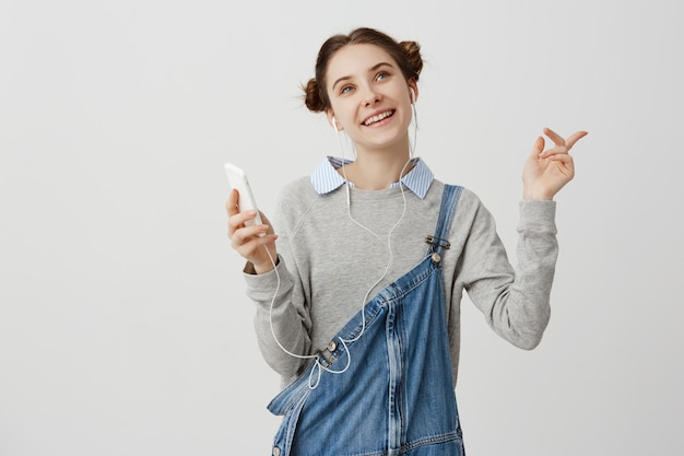 喜んで身振りで示す彼女の携帯電話から音楽を聴いて笑顔の二重パンの髪のかわいい大人の女の子。イヤホンを使って音楽を聴いて満足している女性。娯楽のコンセプト