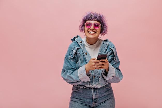 サングラスで明るい散髪のかわいい大人の女性は笑います。電話を保持している巻き毛の女性の笑顔。