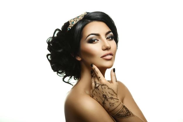 頭に王冠とスタジオの白い背景で隔離の美しい創造的な髪型を持つかわいい大人の王女