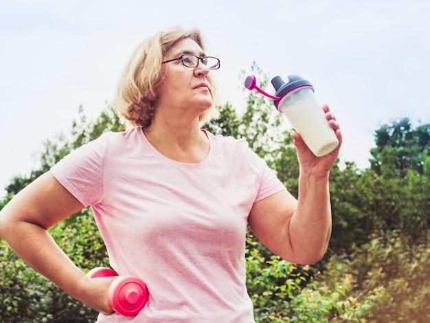 晴れた晴れた日に青い空と緑の木々の公園で運動をしているかわいい、大人の女性。健康的なライフスタイルと長寿の概念