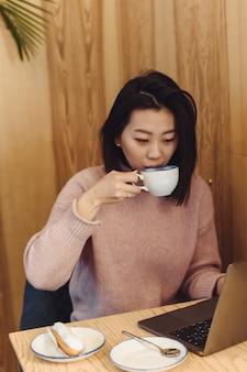 Милая взрослая женщина играет в ноутбуке в кафе. азиатская женщина работает в кафе на ноутбуке. внештатная концепция