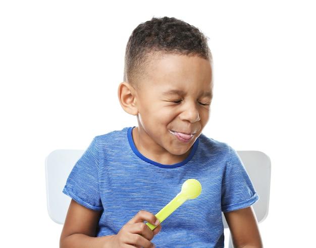 흰색 바탕에 요구르트를 먹는 귀여운 아프리카 계 미국인 소년