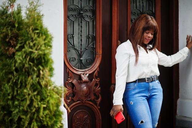 手元の携帯電話で屋外でポーズをとった白いシャツとジーンズのズボンのかわいいアフリカ系アメリカ人モデル。