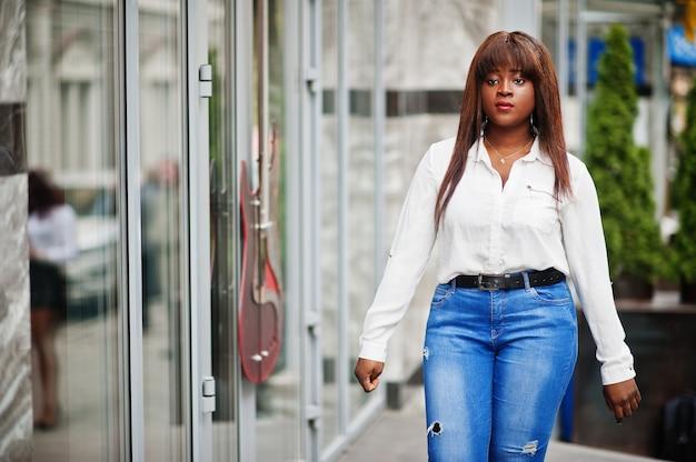 白いシャツとジーンズのズボンのかわいいアフリカ系アメリカ人モデルが屋外でポーズをとった。