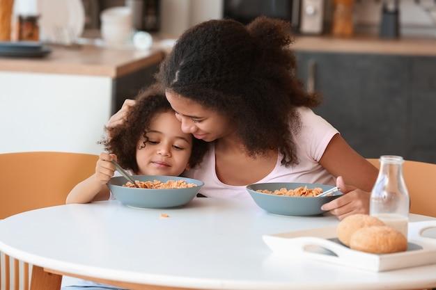 집에서 아침을 먹고 귀여운 아프리카 계 미국인 자매