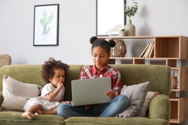 自宅で漫画を見ているラップトップを持つかわいいアフリカ系アメリカ人の姉妹