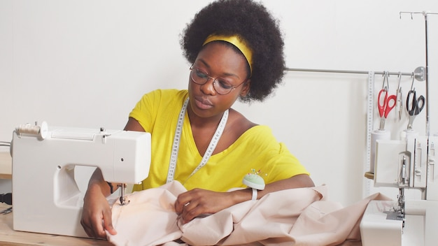 Милая афроамериканка с помощью швейной машины шьет одежду