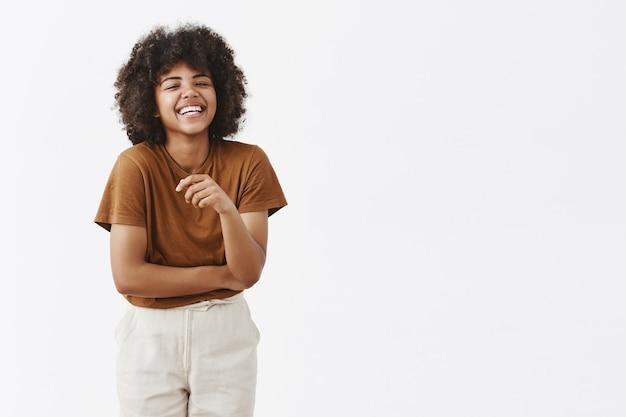 Милая афро-американская женщина с афро-прической в модном летнем наряде весело смеется от радости и весело жестикулирует ладонью, посмеиваясь и беззаботно улыбаясь