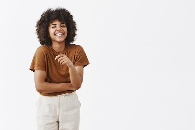 Cute african american woman with afro hairstyle in trendy summer outfit having fun laughing out loud from joy and funny joke gesturing with palm chuckling and smiling carefree