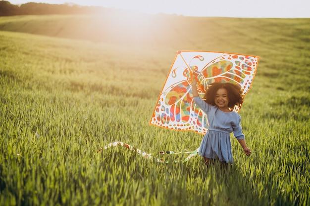 Милая африканская девочка на поле на закате, играя с воздушным змеем