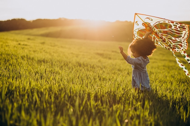 Cute african baby girl at the field on the sunset playing with kite