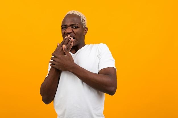 分離された黄色のあくび白いtシャツでかわいいアフリカブロンド男