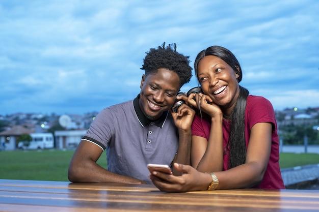公園に座って、一緒に面白いビデオを見ているかわいいアフリカのカップル