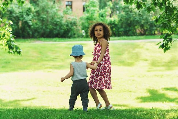 都市公園でかわいいアフリカの女の子と小さな白人の男の子