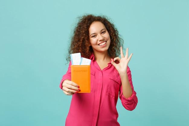 분홍색 캐주얼 옷을 입은 귀여운 아프리카 소녀는 ok 제스처, 여권, 파란색 청록색 배경에 격리된 탑승권을 보여줍니다. 사람들은 진심 어린 감정 라이프 스타일 개념입니다. 복사 공간을 비웃습니다.