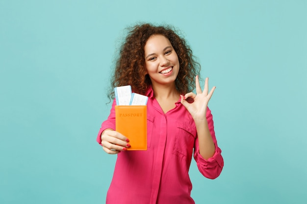 Cute african girl in pink casual clothes showing ok gesture, hold passport, boarding pass ticket isolated on blue turquoise background. people sincere emotions lifestyle concept. mock up copy space.