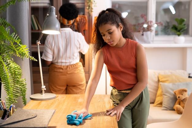 Милая африканская девушка протирает деревянный стол тряпкой, пока ее мать чистит стекло шкафа с книгами в гостиной на заднем плане