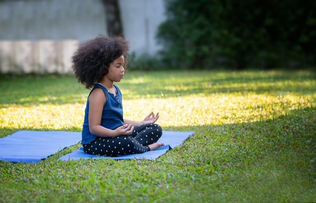 庭のヨガマットで瞑想をしているアフロ髪のかわいいアフリカの女の子。