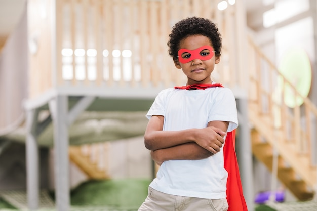 Симпатичный африканский маленький мальчик в белой повседневной одежде и красной мантии супермена смотрит на вас во время игры в детском саду
