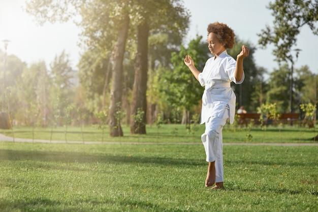路上で瞑想する着物姿のかわいいアフリカ系アメリカ人の女の子