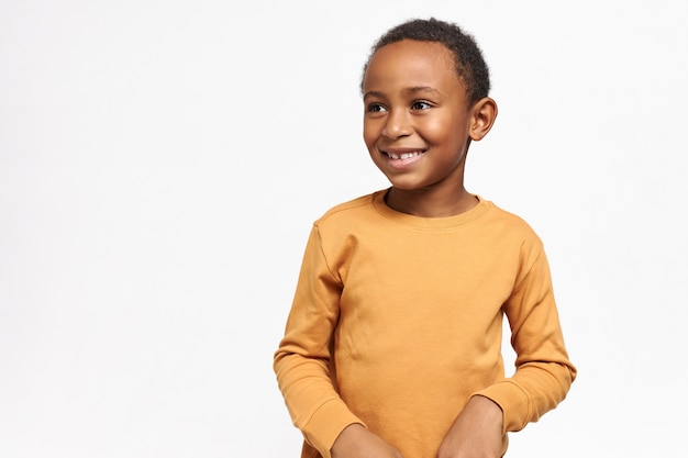 Cute afro american schoolboy in yellow sweatshirt posing against white wall with copy space for your information