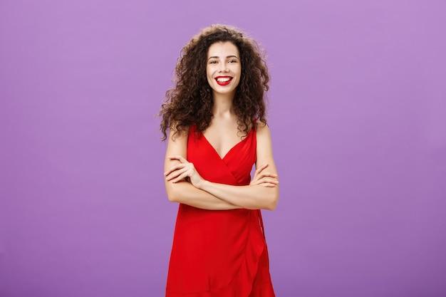 紫色の背景の上で卒業を祝うパーティーを持って広く笑っている自信のあるジェスチャーで手を交差させた豪華な赤いドレスを着たかわいい野心的で幸せな格好良いヨーロッパの女性。