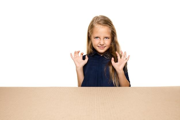 Милая и удивленная маленькая девочка открывает самый большой пакет. возбужденная молодая женская модель на картонной коробке