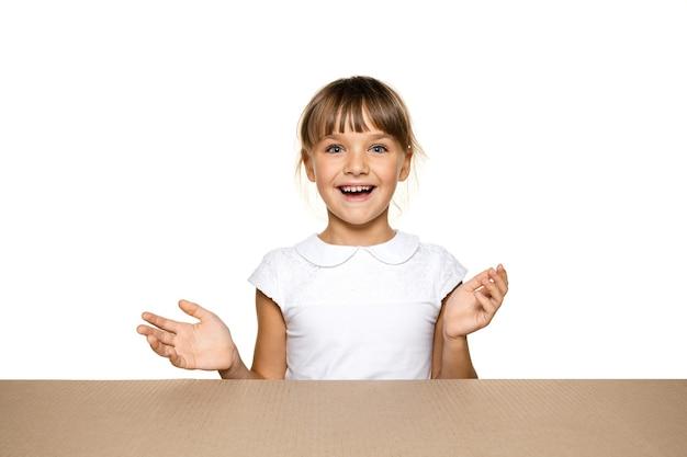 Милая и удивленная маленькая девочка открывает самый большой пакет.