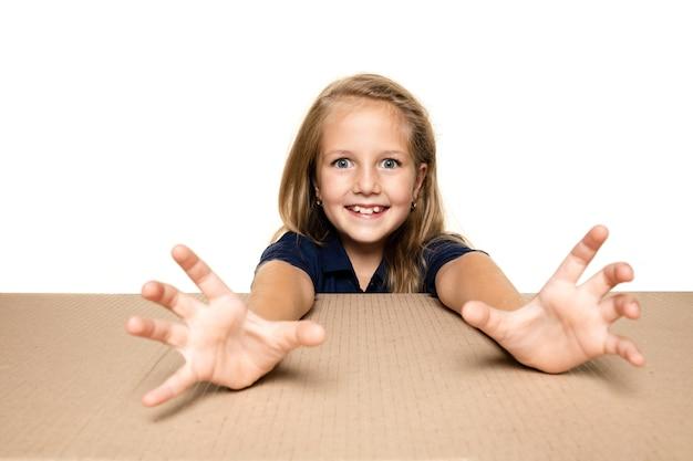 Милая и удивленная маленькая девочка открывает самый большой почтовый пакет. возбужденная молодая женская модель на картонной коробке, глядя внутрь.