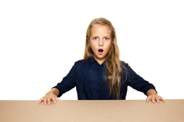 Милая и удивленная маленькая девочка открывает самый большой почтовый пакет. возбужденная молодая женская модель на картонной коробке