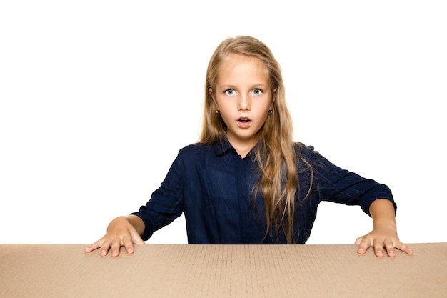 가장 큰 우편 패키지를 여는 귀엽고 놀란 어린 소녀.
