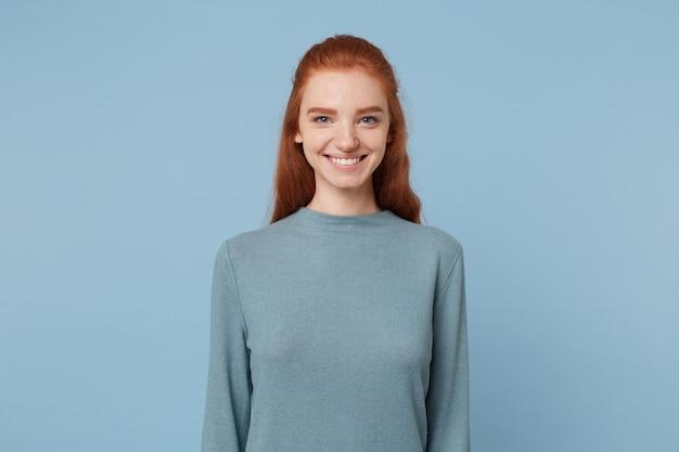 青い壁に隔離されたカジュアルな服を着た赤い髪と青い目を持つキュートで魅力的な女性