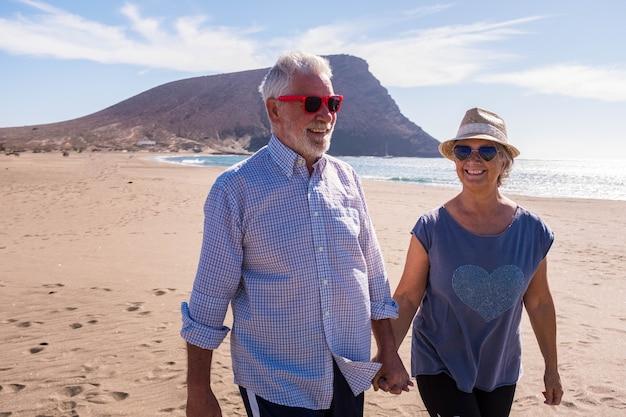 귀엽고 아름다운 노인 부부가 함께 즐거운 시간을 보내고 해변에서 휴가를 즐기고 모래 위를 걷고 웃고