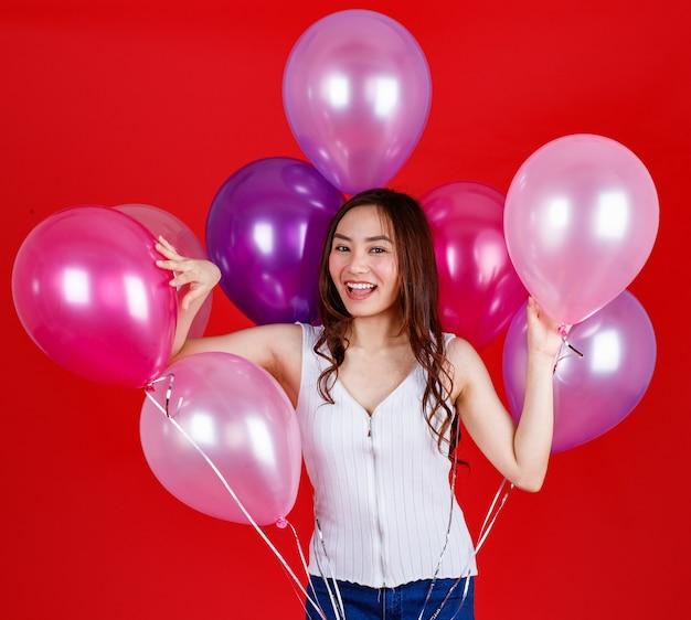 キュートで美しい長い黒髪のアジアの女の子は、赤い背景、スタジオの光の撮影で面白いと幸せな笑顔でカラフルな気球を持って遊んでいます。