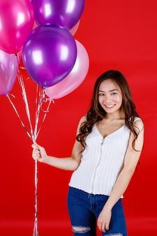 Симпатичные и красивые длинные темные волосы азиатская девушка держит и играет с красочными воздушными шарами с забавной и счастливой улыбкой на красном фоне, студийная световая съемка.