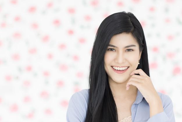 キュートで美しい若い黒人の長い髪のアジア人女性が立って笑顔で自信を持ってフレンドリーなポーズでカメラを見てください。