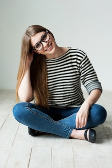 キュートで軽薄。堅木張りの床に座って、あごに手をつないでいる縞模様の服を着た美しい若い女性