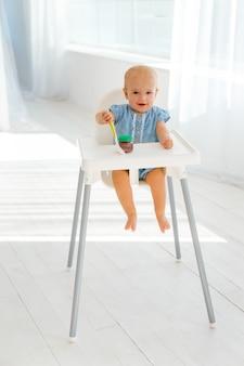 Милый и забавный малыш с пластиковой ложкой на столе для кормления