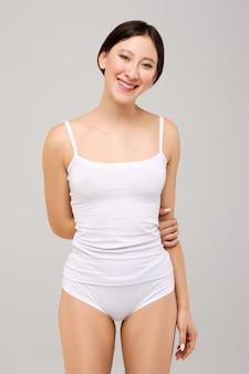 Милая и счастливая азиатская девушка в белой футболке и натуральном гриме