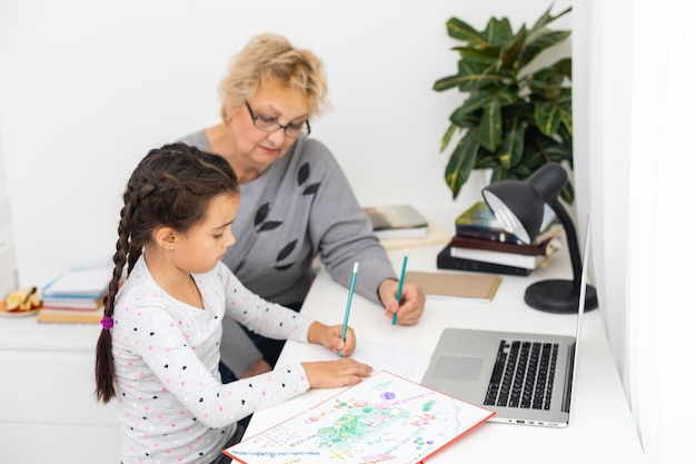 Симпатичная и счастливая маленькая девочка, использующая портативный компьютер со своей бабушкой, обучается через систему электронного обучения онлайн.