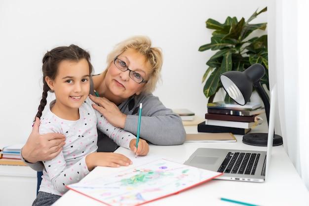 オンラインのeラーニングシステムで勉強している、おばあちゃんと一緒にラップトップコンピューターを使用しているキュートで幸せな小さな女の子。