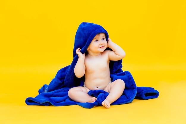 11개월 된 귀엽고 건강한 아기는 노란색 배경에 앉아 후드가 있는 파란색 수건으로 싸여 있습니다.