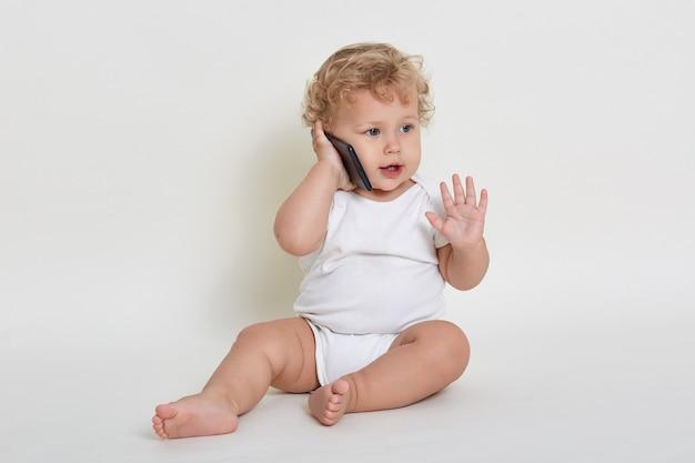 Милый и радостный мальчик играет, разговаривает с кем-то через смартфон, сидя в помещении на полу, глядя в сторону и поднимая ладонь вверх