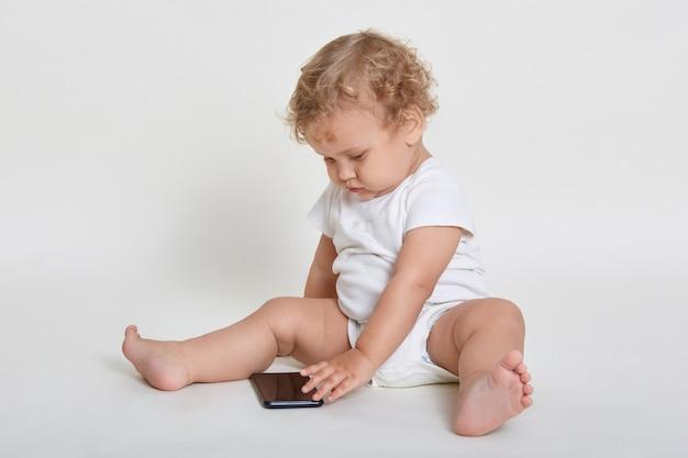 Милый и радостный мальчик играет со смартфоном, сидя в помещении на полу