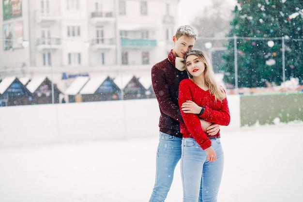 Милая и любящая пара в красных свитерах в зимнем городе