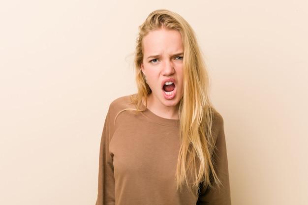 非常に怒って攻撃的な悲鳴を上げるキュートで自然な10代の女性。