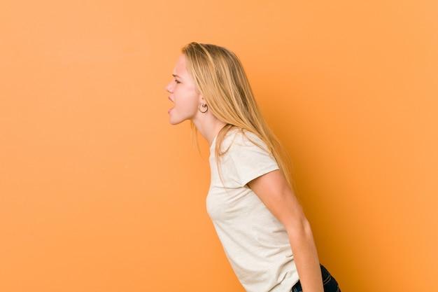 コピースペースに向かって叫んでいるキュートで自然な10代女性